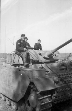 Panzer III & its crew. One crew member has the Tank Destruction award on his right sleeve. Also notice the driving lights are on.