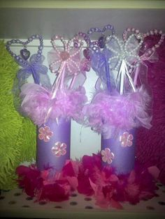 Princess wand holders.  So easy to make... we used the lays stack potato chip plastic containers, construction paper, hot glue and dollar store feather boas and weighted them down with some fish tank rocks. The flowers came from an old dress up costume. And dollar tree wands. Cheap, easy and perfect for a princess party. I think they turned out cute!!