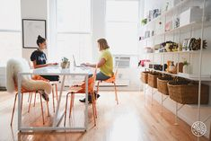 """The New Man Repeller Office - The workspace is kept tidy with full-wall shelving from <a href=""""http://www.bludot.com/modern-office-furniture/modern-office-storage-shelving/hitch-addon-bookcase.html"""" target=""""_blank"""">Blu Dot</a> - @Homepolish New York City"""