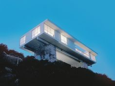 Two 84-foot long steel beams span two concrete towers, lofting the 2000 square foot single-family house above a steeply sloping lot in Pasadena, California.