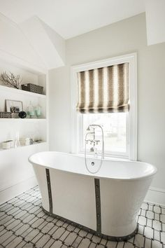 """An eye catching Nautica 68"""" Cast Iron French Bateau Tub sits on black and white geometric floor tiles and is paired with a polished nickel vintage style hand held tub filler fixed in front of a window dressed in a black and white roman shade framed by an off-white wall painted in Benjamin Moore White Wisp."""