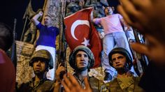 Turkish solders at Taksim square in Istanbul are surrounded by pro-government demonstrators early Saturday. (AFP/Getty Images)