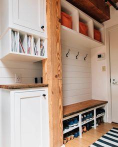idée entrée avec des éléments boisés, meubles blancs, cases de rangement oranges, sol en bois PVC, banc recouvert de grand coussin rectangulaire aux motifs de grand tronc d'arbre, tapis aux rayures horizontales bleues et blanches