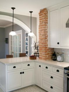 An original brick pillar, which was previously concealed behind wallboard, is now exposed, adding visual interest and texture to the kitchen space.