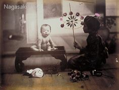 A girl tries to make a baby placed on a canopy happy with toys. She has many toys beside her. It is not known why the baby is placed on a canopy, but it is a humorous photo. about 1870's by photographer Suzuki,Shin-ichi