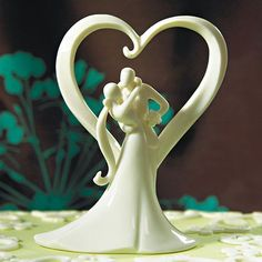 Bride and Groom Cake Topper Figurine - the bride and groom standing under a heart arch. Stylized Porcelain Wedding Cake Toppers for Traditional and Themed Weddings.