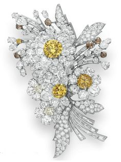 A COLORED DIAMOND AND DIAMOND FLOWER BROOCH, BY BVLGARI   Mounted en tremblant, designed as three variously-shaped diamond flower blossoms, set with a circular-cut fancy vivid yellow diamond pistil, weighing approximately 3.38 carats, and two smaller circular-cut yellow and brown diamond pistils, enhanced by numerous circular-cut brown diamonds, with circular and baguette-cut diamond leaves and stems, mounted in platinum, 1959  By BVLGARI. Elizabeth Taylor Collection