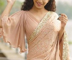 Latest Bell Sleeves Saree Blouse Designs Bell sleeves have come back in trend again. And this is not just seen in the Western clothing but even for the saree blouse designs. In the recent times, you might have seen bell sleeves saree blou… Saree Jacket Designs, Saree Blouse Neck Designs, Fancy Blouse Designs, Bridal Blouse Designs, Pink Saree Blouse, Choli Blouse Design, Peach Saree, Blouse Dress, Sleeves Designs For Dresses