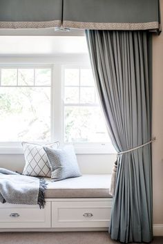 Window seat - blue and neutrals, storage beneath with the curtains arranged  to frame the seat and the view.