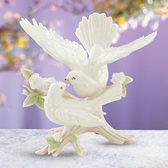 A pair of sculptured doves perched on a rose bush, sharing a loving embrace. This romantic scene is captured in Lenox fine china. Three hand-formed roses are abloom on the bush, each painted by hand in delicate hues of pink over white.