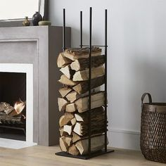 This steel log holder maximizes vertical space, storing firewood in a slim stack beside your hearth. Its no-frills, open build and four divider bars keep the presentation neat.