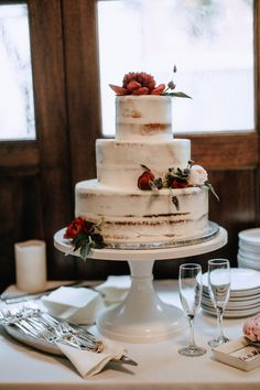 Nearly naked three-tiered wedding cake w/ red floral decorations | Image by Joseph West Photography