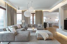 salon contemporain avec éclairage indirect aménagé avec des canapés gris clair et une table basse blanche