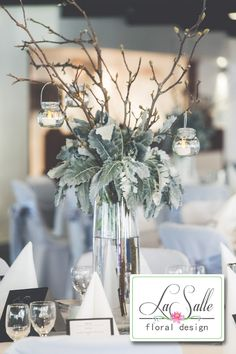 Who says you need to use flowers in your centrepieces?  The bare magnolia branches are surrounded by silver suede (dusty miller) foliage in this piece, all set in a tall glass cylinder vase with three small jars hanging from the branches.  Photography by Oy Photography (www.oyphotography.com.au).  Floral design by LaSalle Floral Design (www.lasallefloraldesign.com).