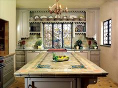 Spanish Kitchen Makeover. Salvaged tile, leaded glass windows, and vintage lighting transform a Spanish Revival kitchen from eyesore to showstopper.