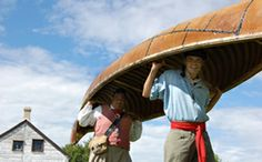 Costumed guides carry a canoe at Lower Fort Garry National Historic Site | St. Andrews, Manitoba