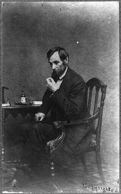 [Abraham Lincoln, seated next to small table, in a reflective pose, May 16, 1861 wem