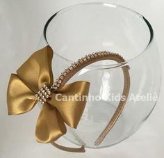 Linda tiara encapada de cetim na cor dourada com detalhes strass.