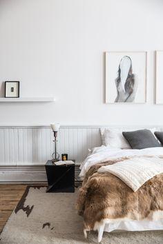 fur on bed, wooden panneling, black side table, rug