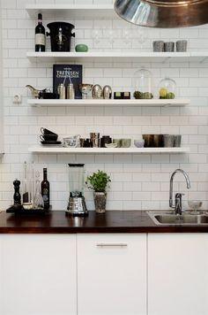 Kitchen shelves.  Brick tiles.  Wooden benchtops.