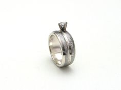 http://www.jloose.com/siteimages/sankey.b.2.15.15.jpg A handmade, sole-authored engagement / wedding band in stainless damascus, fused together to look as one, in Sterling silver and with a prong-set diamond.