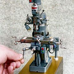"""An even smaller 1/14 scale functional Bridgeport by Barry Jordan. """"It took 17 weeks (640 hours) to complete. It stands only 7.8"""" high and was made from cast iron billet material. It runs on a miniature Swiss 1.5 Volt DC motor that Barry runs using 3 VDC."""" SHIT!"""