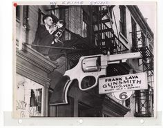 My Crime Studio - Weegee on a ledge above the Frank Lava Gunsmith shop, at 6 Centre Market Place, presumably waiting for some action across the street at Police Headquarters. His studio was located in the building on the right.