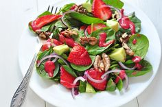 Crisp spinach, avocado, and sweet strawberry combine for a refreshing summer salad.