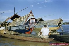 Man sits in canoe near large boat with painted stern. Palembang, Sumatra, Indonesia. (Date: 1/1/1951)