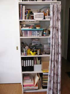 Hide the clutter!   Use a tension rod, half a shower curtain and curtain hooks to hide the clutter on a bookshelf!