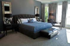 Brown headboard with black nightstands against a dark gray accent wall.
