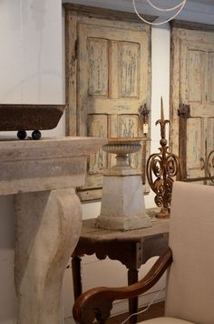 Love all of these great items.....distressed doors, metal urns, candlesticks, limestone mantel...all at Wilson Antiques