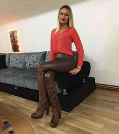 Amateur in brown leather pants and OTK boots seated on couch