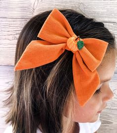 Sep 4, 2020 - This fall bow is the perfect hair accessory for the pumpkin patch! This is a sailor bow with a pumpkin charm attached to the middle. This is a soft orange color. It is attached to an alligator hair clip. Not only is it for the pumpkin patch, but it is an absoutle staple to be apart of your girls fall hair acessories!