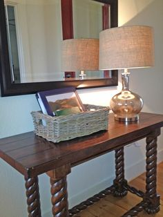 Glass Lamp with Burlap Shade (Hobby Lobby), Grey Basket (Target), Simple Black Framed Beveled Mirror (Home Depot) above the table in the foyer.