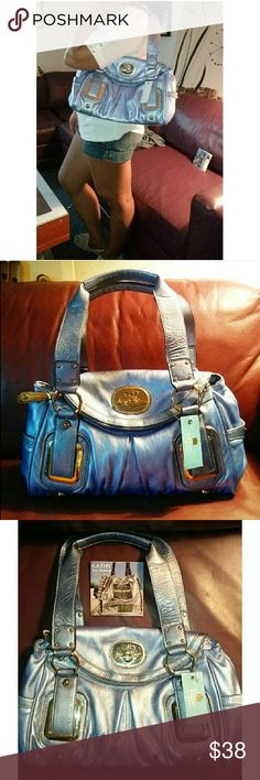 🆕 ▪ Kathy Van Zeeland Periwinkle Bag ▪ Brand New with tag & seller card still on bag. Beautifully metallic periwinkle blue/purple shoulder bag. Gold hardware. Features a lot of storage compartments. 2 on each side of outside, 2 little compartments on inside as well as a zipper compartment. The flap of the bag that secures the handbags's closure is also a hidden storage compartment that is closed by zipper.  This is the perfect size bag. Kathy Van Zeeland Bags