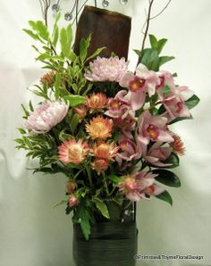 Pretty pink table arrangement filled with long lasting cymbidium orchid, paper daisy and disbud, decorated with husk and sticks
