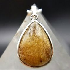 Say hello to this precious Golden Rutilated Quartz pendant set in sterling silver. This mesmerizing pear shaped pendant has dense beautiful strands of golden rutile, also known as angel hair, that shine and glimmer under sunlight! You will appreciate this pendants chunky cabochon that is domed and polished on both sides unlike pendants that are flat on the back. This crystal is one of my go to favs for manifesting abundance and prosperity. Wear this pendant to help set an intention for more…