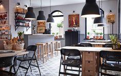 Ravintola, jossa koivuiset pöydät ja baarijakkarat ja mustat tuolit.