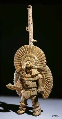 Western Mexico, Colima. clay. Warrior waering feathered backrack. He carries an atl-atl in the shape of a bird and darts in his left hand.