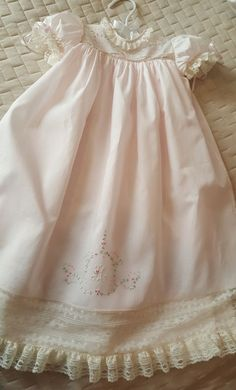 This beautiful long baby dress was designed to be worn by a baby girl then to be shortened at a later date as she begins to walk. This dress would also be perfect in white for a baby dedication or christening. The dress pictured is created using pale pink Swiss batiste and ecru French Maline laces. The yoke features pastel hand embroidery consisting of pink bullion roses and greenery. The bottom of the front and back yokes are bordered with a narrow French Maline lace insertion and the neck…