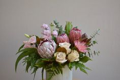 Long lasting locally grown proteas, with fragrant stock, roses & lisianthus in a soft sage ceramic pot.