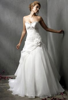 "Elegant wedding dress. Sweetheart neckline fitted bodice and full flouncy skirt. Love the piece that comes up and across and is ""pinned"" to the hip with floral flower- a beautiful tribute to the female form  #wedding dress"