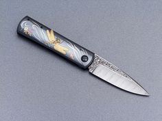 Knife by: Fred Carter Blade length: 80 mm Overall length: 180 mm Materials: damascus, gold, anodized titanium, silver.
