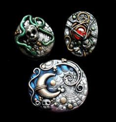 Made by Mandarin Moon from polymer clay. The largest piece features a sterling silver moon. Of the smaller two, one features a snake coiling around a skull and the other has a blood red glass gem trapped under a net and guarded by a skull