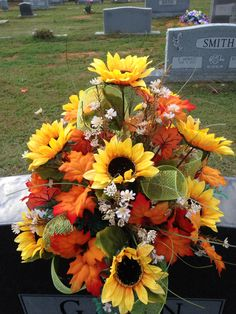 Fall cemetery vase using Sunflowers, mixed leaves, cream filler flowers with lime green shiny ribbon. November 2015.