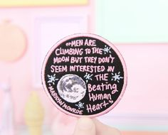 "Sew-on embroidered patch featuring Marilyn Monroe's quote, ""Men are climbing to the moon but they don't seem interested in the beating human heart."""