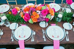 Pink, orange and purple centerpieces with pink satin napkins and clear beaded charger plates at a Disneyland wedding reception