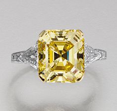 FINE FANCY VIVID YELLOW DIAMOND RING, TIFFANY & CO.  The fancy vivid yellow step-cut diamond weighing 4.55 carats, set between triangular stone shoulders, mounted in platinum,  signed Tiffany.