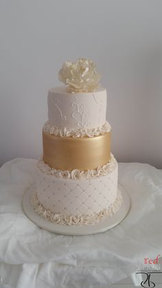 Clare's amazing cakes. 3 tiers with the gold and bottom with ruffles.